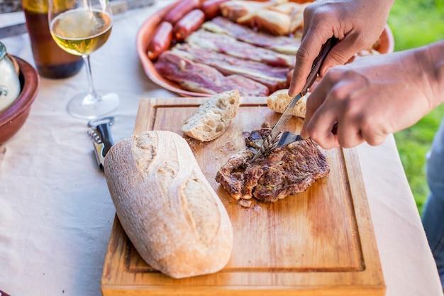 Mão de uma pessoa que corta bife grelhado na tábua de cortar com garfo e faca