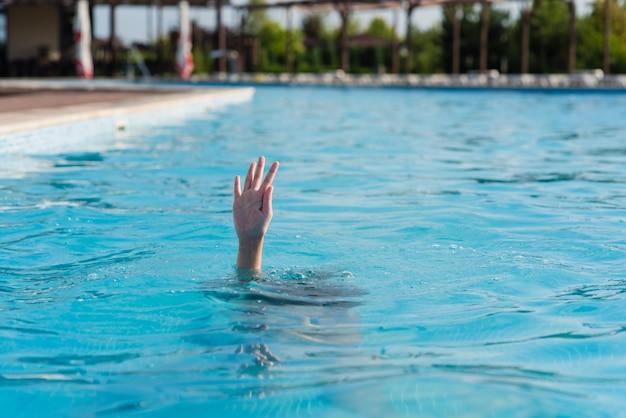 Mão de uma pessoa se afogando em uma piscina