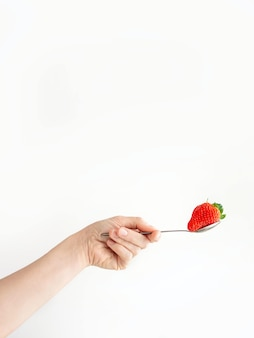 Mão de uma pessoa segurando uma colher com um morango em uma superfície branca