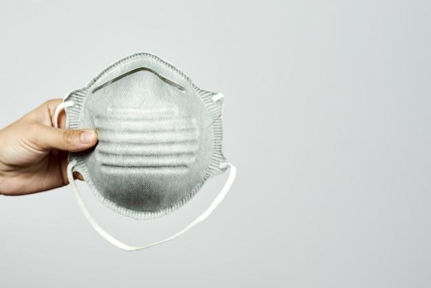 Mão de uma pessoa segurando uma máscara de proteção pessoal