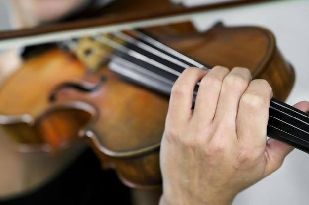 Mão de uma violinista na escala de um violino tocando um acorde durante a apresentação musical de perto