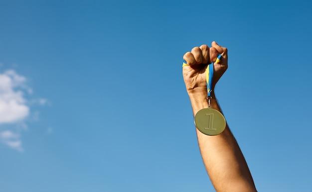 Mão de vencedor levantada e segurando a medalha de ouro com fita contra o céu azul. medalha de ouro é a medalha concedida à maior conquista no esporte ou nos negócios. conceito de prêmios de sucesso