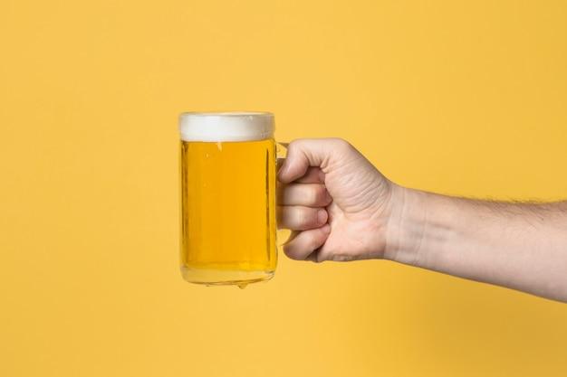 Mão de vista frontal com caneca de cerveja