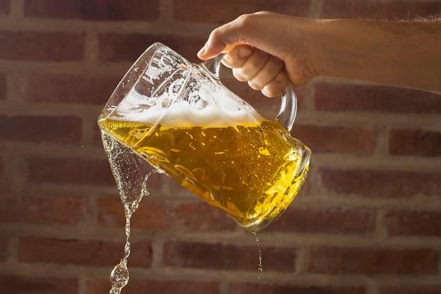 Mão de vista frontal com cerveja derramando cerveja