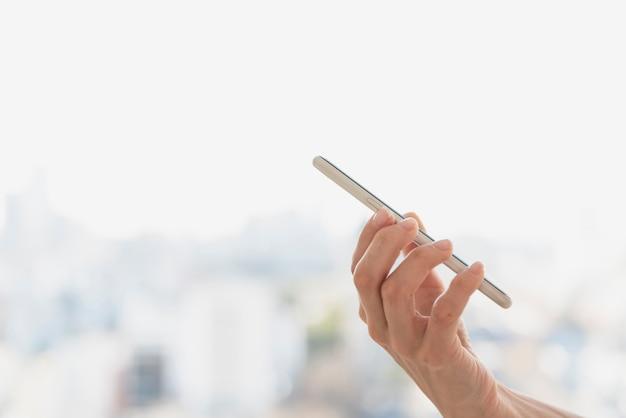 Mão de vista lateral, segurando o telefone com fundo desfocado