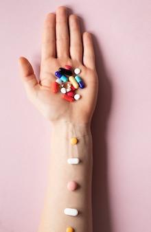 Mão de vista superior com analgésicos coloridos