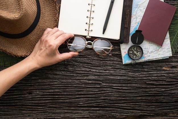 Mão de vista superior do explorador agarrar óculos para viajar