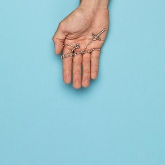 Mão de vista superior, segurando o colar sagrado