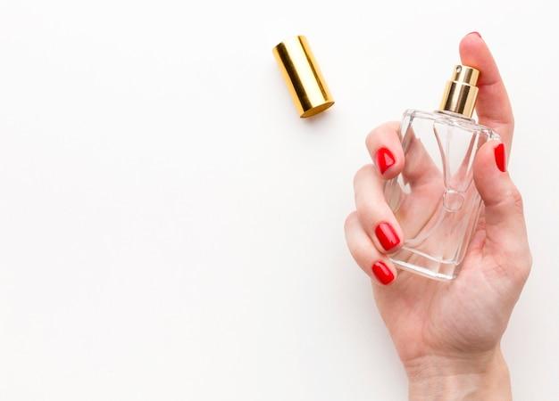 Mão de vista superior, segurando o frasco de perfume com espaço de cópia