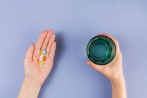 Mão de vista superior, segurando o medicamento e copo com água