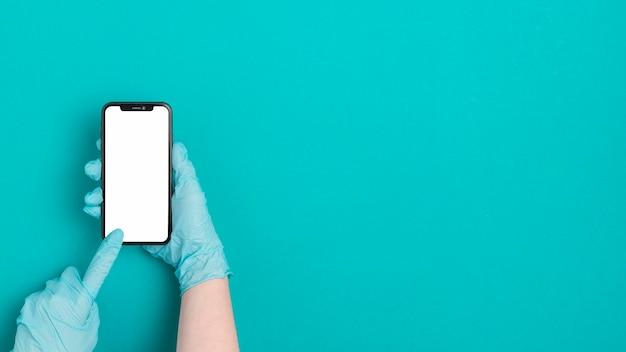 Mão de vista superior, segurando o telefone móvel com espaço de cópia
