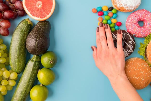 Mão de vista superior, separando alimentos não saudáveis de frutas e legumes