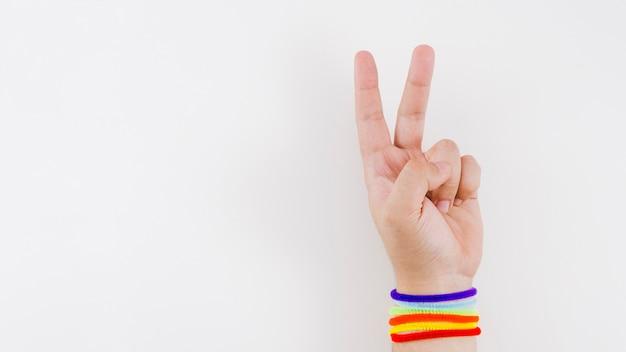 Mão de vitória com pulseira de bandeira do orgulho