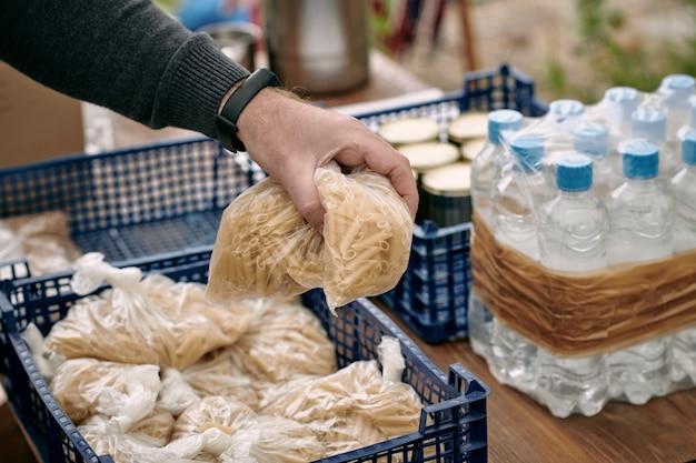 Mão de voluntário pegando sacos com macarrão para migrantes
