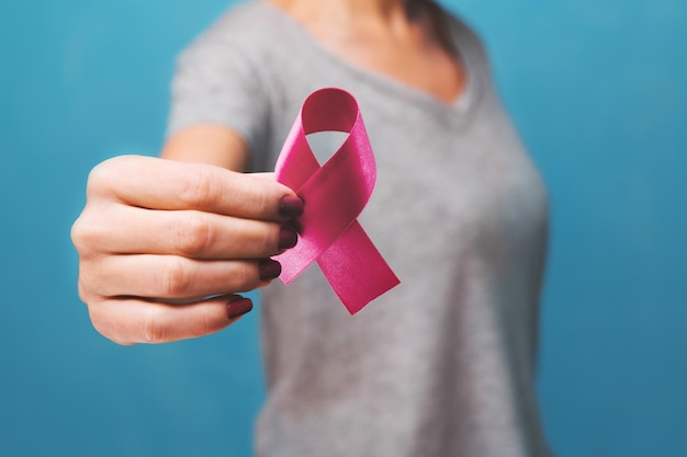 Mão de womaen segurando fita rosa de conscientização do câncer de mama. conceito de saúde e medicina