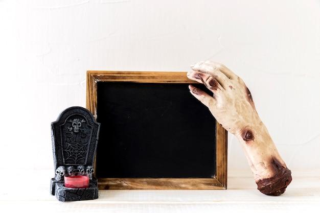 Mão de zumbi e lápide perto de quadro-negro