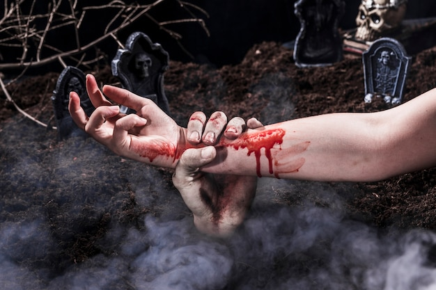 Mão de zumbi segurando o braço da mulher ensanguentada no cemitério de halloween