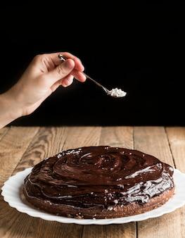 Mão decorando bolo de chocolate com flocos de coco