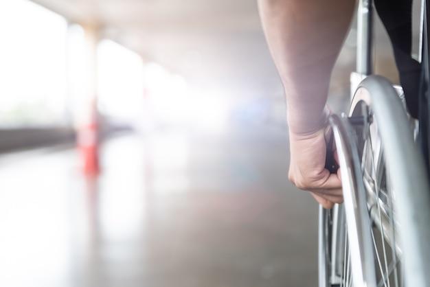 Mão deficiente do homem do close up na roda da cadeira de rodas.