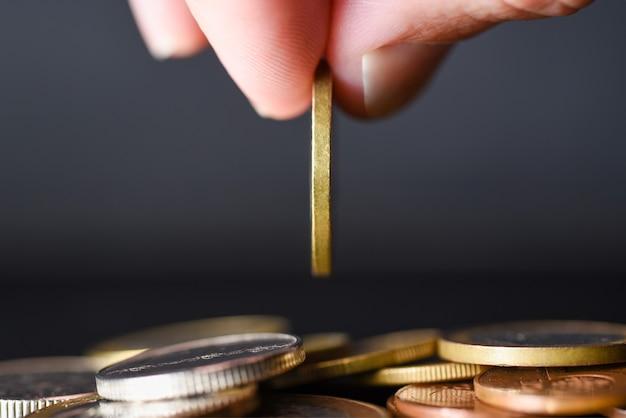 Mão deixa cair uma moeda em uma pilha de moedas em um fundo preto.