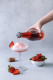Mão derrama champanhe rosa em um copo com sorvete de morango em uma superfície cinza. o conceito de deliciosas bebidas. copie o espaço.