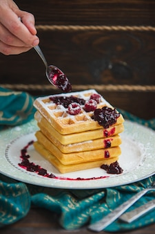 Mão derrama geléia na pilha de waffles com uma colher.