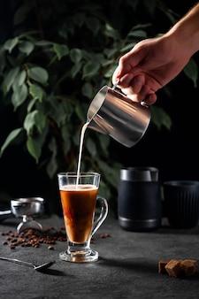 Mão derrama leite na xícara com café preto