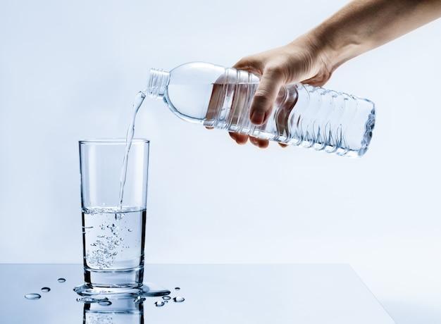Mão derramando água pura e fresca da garrafa em um copo na mesa com gotas de água, cuidados de saúde e conceito de hidratação de beleza