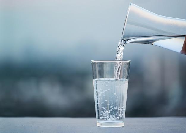 Mão derramando beber água da garrafa no copo