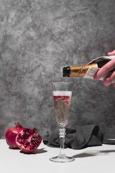 Mão derramando champanhe em vidro
