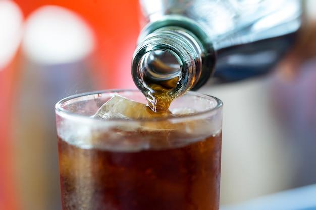 Mão derramando copos de garrafa de coca-cola.