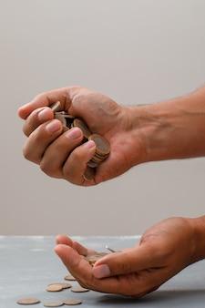Mão derramando moedas em outro.