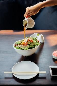 Mão derramando molho de salada de gergelim na salada japonesa.