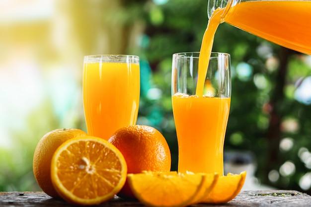 Mão derramando suco de laranja em copos