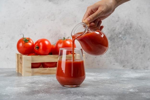 Mão derramando suco de tomate em um copo de vidro.