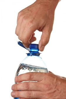 Mão desapertar a rolha em uma garrafa de água isolada