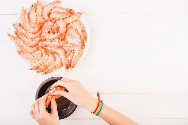 Mão descascando camarão na mesa da cozinha