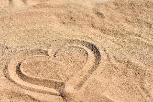 Mão desenhada coração na areia do mar na praia