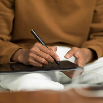 Mão desenhando com caneta na mesa gráfica de perto