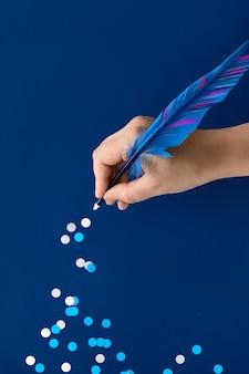Mão desenhando trilha de flocos de neve de papel da pena de penas azuis