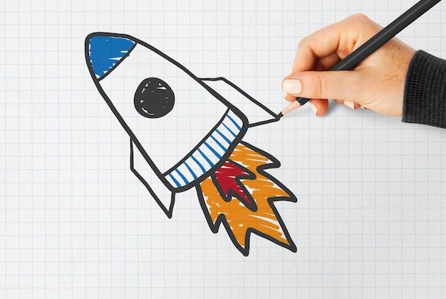 Mão desenhando um lançamento de foguete em um papel de caderno