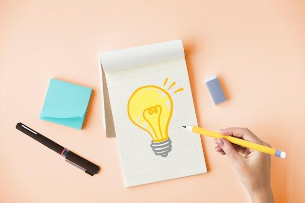 Mão desenhando uma lâmpada em um bloco de notas