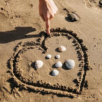 Mão, desenho, coração, areia