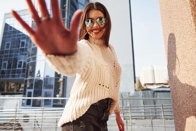 Mão desfocada. linda jovem com roupas quentes passeava pela cidade nos fins de semana