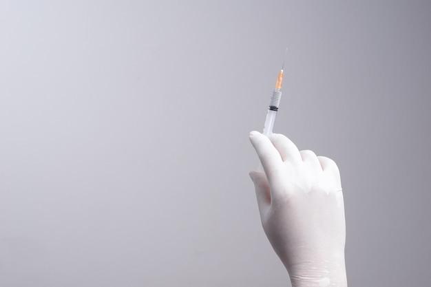 Mão, desgastar, luva latex, segurando, siringa, com, um, medicina