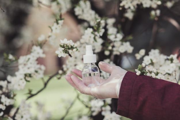 Mão desinfetante dispensador florescendo fundo de árvores