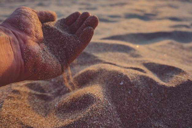 Mão despeja areia.