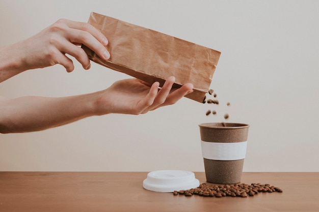 Mão despejando grãos de café de um saco de papel em uma xícara de café