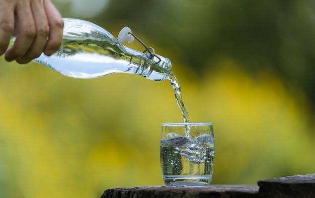 Mão, despejar, beba, água, de, garrafa, em, vidro, com, natural, fundo
