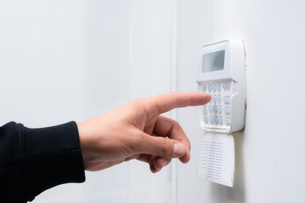 Mão digitando a senha do sistema de alarme de um apartamento ou escritório